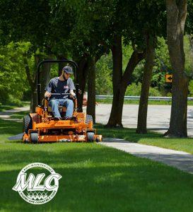 scag mower mowing next to sidewalk