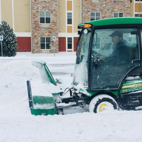 Enclosed John Deer tractor with Snow Blower in winter